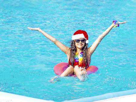 Beautiful young woman in Santas hat with inflatable donut in swimming pool