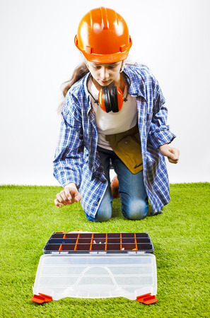 A young female construction worker chooses a tool for work in a box. Building concept Stock Photo