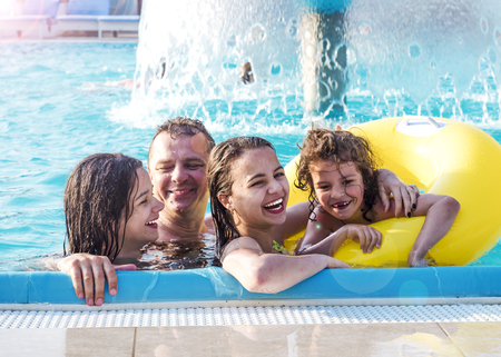 Father and children playing in the swimming pool at the day time. People having fun outdoors. Concept of happy family. Stock Photo