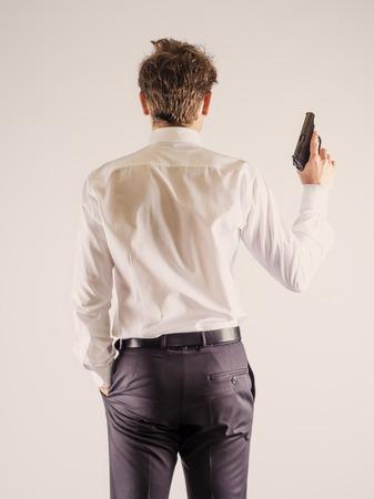 One caucasian spy criminal policeman detective man holding gun portrait silhouette in studio isolated white background Reklamní fotografie