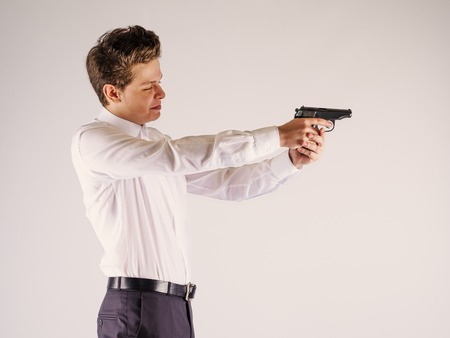 One caucasian spy criminal policeman detective man holding gun portrait silhouette in studio isolated white background Stock Photo