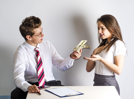 The concept of gratitude. Young handsome man giving money to a beautiful governess. Gray background. Stock Photo