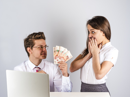 The concept of gratitude. A young handsome man gives money to a beautiful stockbroker. Gray background.