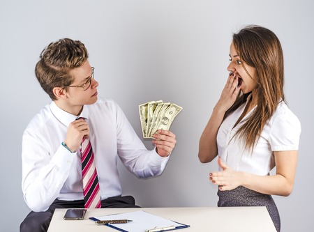The concept of gratitude. Young handsome man giving money to a beautiful colleague. Gray background.
