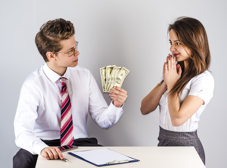 The concept of gratitude. Young handsome man giving money to a beautiful manager. Gray background. Stock Photo