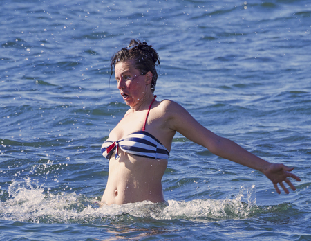 The young woman is very frightened. In the ocean. She took her hands back.