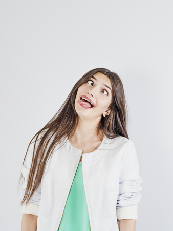 The girl makes a funny face. Her eyes are looking inwards Stock Photo