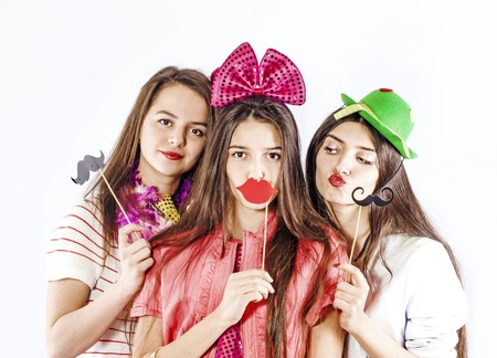 young smiling three girls holding near the face of paper props in the form of lips, mustaches for the photo, isolated on white background Foto de archivo