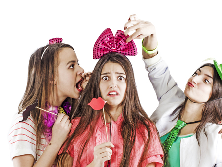 Two girlfriends are trying to scare and embarrass a shy girlfriend at a crazy party. Concept of embarrassment Stock Photo
