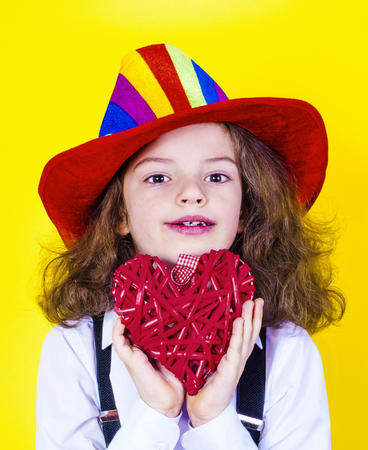 A lovely boy with long hair holds a big red heart