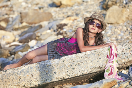 A cute young model posing lies on the stones.