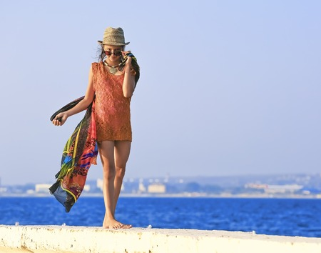 Holidays, vacation travel and freedom concept. Portrait of girl with long hair on seaside. Young woman in summer dress posing on the sea coast