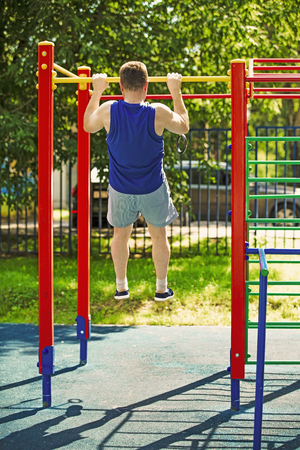 A mature man doing pull-ups at an open gymnastic complex. The concept of a healthy lifestyle