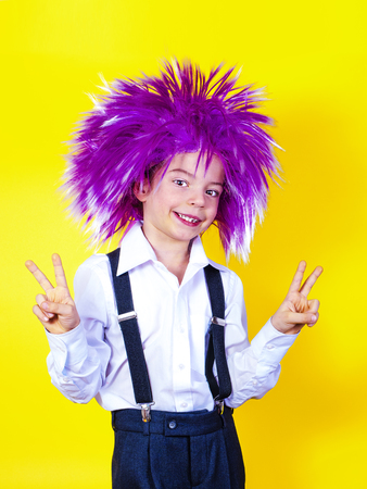 Cute boy in carnival wig. Yellow background. Stock Photo