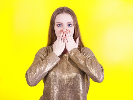 Portrait of a surprised adorable girl with a mouth, an openly yellowed background