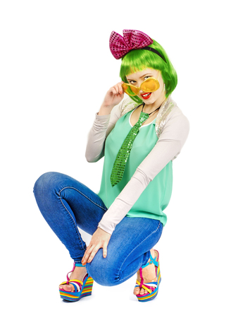 Beautiful young woman in an outrageous outfit spending time in the studio. Attractive Caucasian female model in fashion accessories and green wig, playfully posing Stock Photo