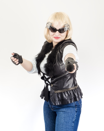 A semi-long portrait of a female rock musician in a black leather jacket and gloves on a gray background. The concept of music and rock style