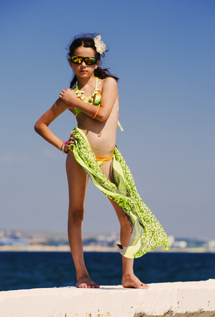 Attractive brunette teenage girl in effective attire posing on the beach by the sea or ocean Banque d'images