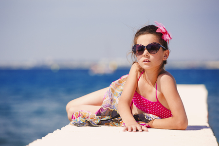 Attractive brunette teenage girl in effective attire posing on the beach by the sea or ocean 写真素材
