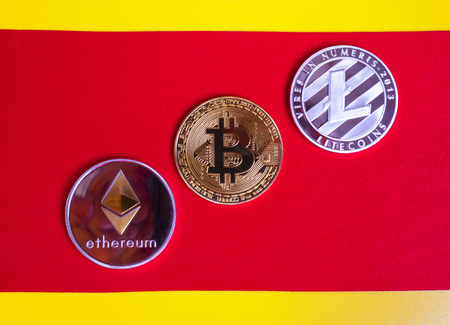 Gold bitkoyny digital virtual money on a red-yellow background. Metal gold money bitkoynju Credit coins - bitcoin BTC , litecoin LTC , ethereum ETH digital cryptococci
