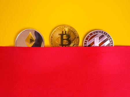 Gold bitkoyny digital virtual money on a red-yellow background. Metal gold money bitkoynju Credit coins - bitcoin BTC , litecoin LTC , ethereum ETH digital cryptococci
