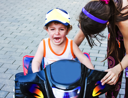A little boy is capricious and crying, sitting on a childrens ATV near the house. Childrens games in the open air, walking and playing with a child on the street Stock Photo