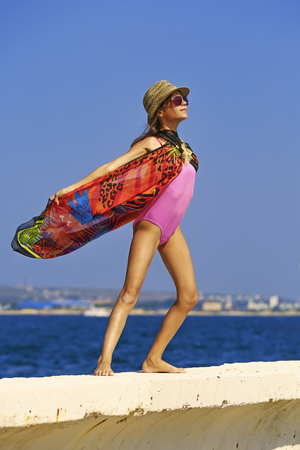 Young and beautiful girl have a seasonal winter vacation on the beach in exotic country