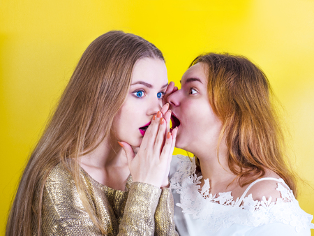 Young girl telling her best friend private secret. Girlfriend listening with surprised expression on face. Best friends gossip about people they know, telling latest rumors, sharing personal news.