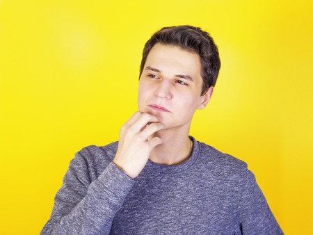 Portrait of a thoughtful young man, isolated on a light background Stock Photo