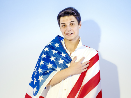 A young handsome man wrapped in a national flag - the United States, laid his hand on his heart. Oath concept Stock Photo