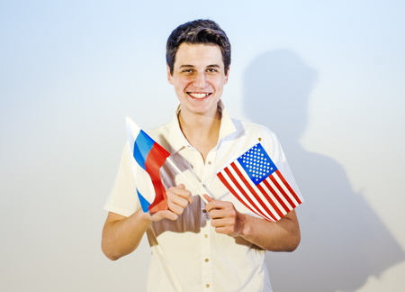 Adorable brunette guy holding the flag of the USA and Russia Stock Photo