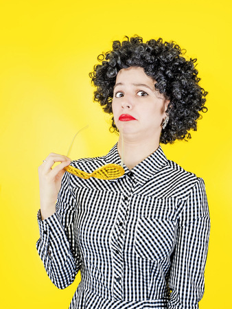 Surprised girl clown with afro wig, isolated on yellow background