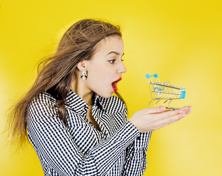 The concept of purchase. Portrait of a excited woman holding a small empty basket on her palm, isolated on a yellow background
