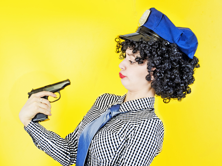 A girl with a gun holding a gun to her head, pretending to be jokingly timidly staring at the barrel of the gun, on a yellow background.