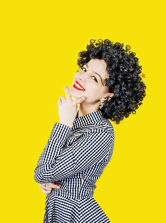 Close-up portrait of a young woman in an afro wig on a yellow background Stock Photo
