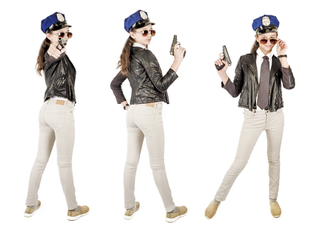 Cute young police girl in black jacket and with pistol posing on white