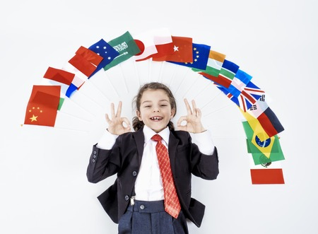 The child makes a gesture Ok under the multitude of flags of various states of the world, the concept of friendship of peoples