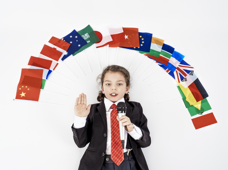 The child lies with a microphone under a lot of flags of different countries of the world and declares the concept of friendship Stock Photo