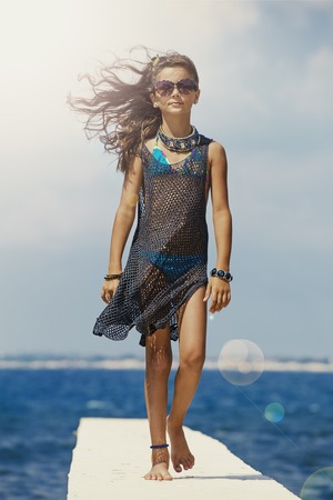 Adorable young girl in a t-shirt mesh posing on the pier