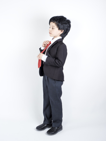 Shot of a cute little boy in a business suit holding a red tie, on a gray background 스톡 콘텐츠