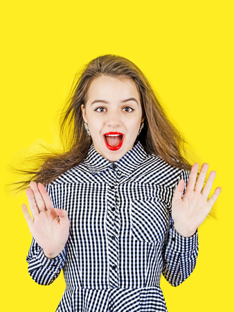 Cute girl in a checkered dress to put his hands forward, to stand with open mouth. Yellow background.