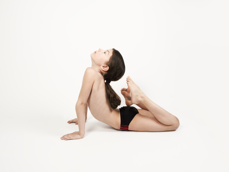 Seven-year-old child practicing yoga on the floor, stretching in raja bhudjangasana exercise, King Cobra pose, wearing swimming trunks on a light background