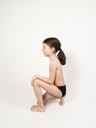 Cute boy with long hair in swimming trunks sits leaning on knee. Light background.