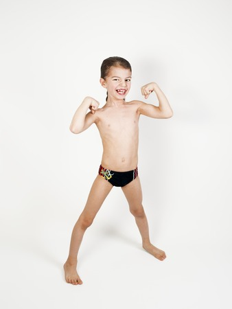 Happy little boy triumphing with raised hands, on a light background 스톡 콘텐츠