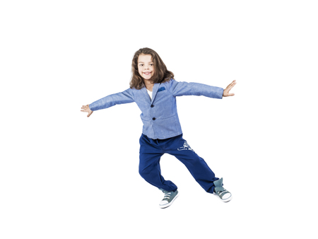 Long-haired preschool boy simulates flight, isolated on white