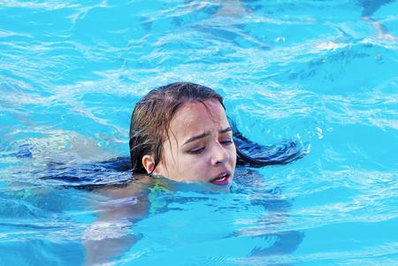 Little girl in danger drowning in the swimming pool Foto de archivo
