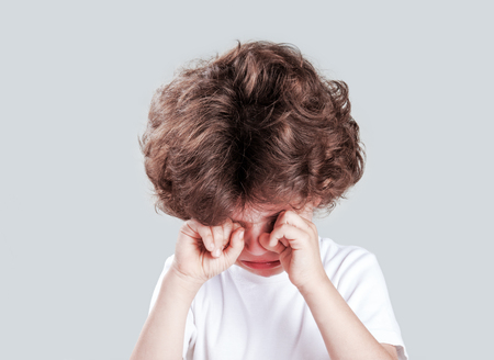 Cute little curly-headed boy in a white t-shirt is crying and looking at the camera. Gray background. Close-up.