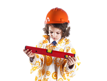 A cute curly-haired boy builder in a raincoat holding a building level.Foreman in an orange construction helmet.