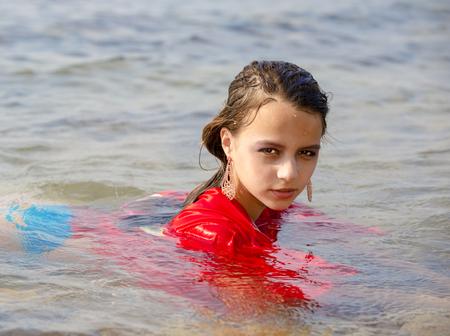 Schattig vrouwelijk meisje gekleed in een rode jurk, baadt leugens in de zee nat en erg mooi Stockfoto