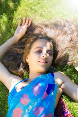 Beautiful young female teenager in bikini and beach shawl enjoying a sunny afternoon on the grass floor Banque d'images